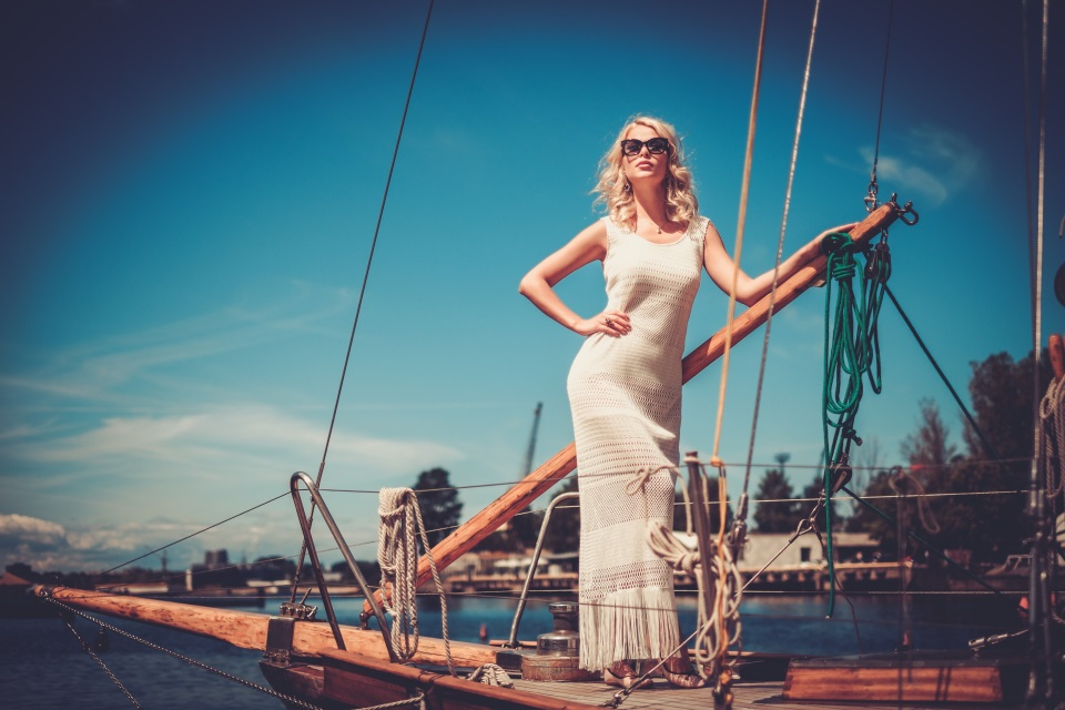 Blond woman in white long dress and sunglasses standing on a yaht.